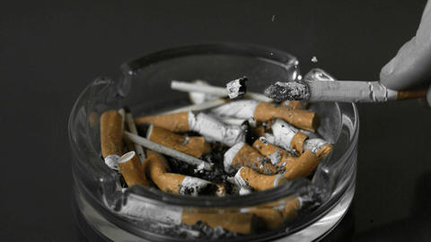 Hand Tipping Ash From Cigarette Into Ashtray stock footage