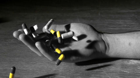 Mans hand falling holding pills after overdose in Stock Video Footage