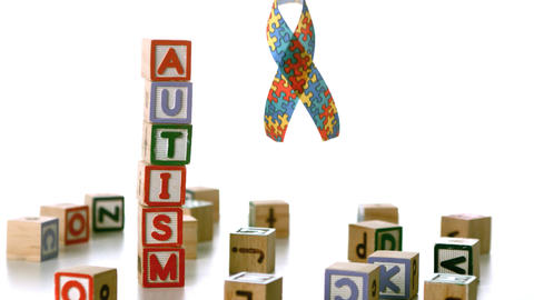 Autism ribbon falling beside blocks spelling autis Footage