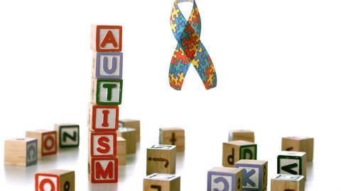 Autism ribbon falling beside blocks spelling autis Stock Video Footage