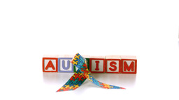 Awareness ribbon falling onto blocks spelling auti Stock Video Footage