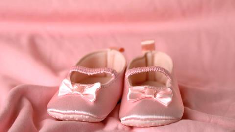 Pink booties falling on pink blanket Stock Video Footage
