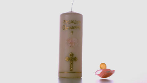 Pink pacifier falling beside baptism candle Stock Video Footage