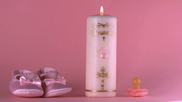 Baby shoes falling beside lit baptism candle and p Stock Video Footage