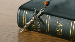 Rosary beads falling onto black bible Footage