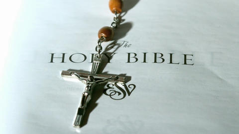 Rosary beads falling onto first page of bible Stock Video Footage