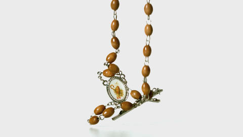 Rosary beads falling onto white surface Stock Video Footage