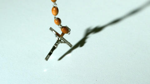 Rosary beads casting a shadow and then falling Footage