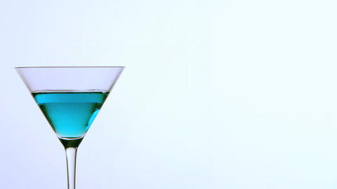 Ice falling into cocktail glass of blue alcohol on Stock Video Footage