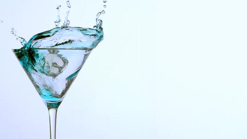 Ice falling into cocktail glass of blue alcohol on Footage