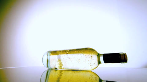 White wine bottle spinning around on white surface Live Action