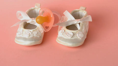 Pink soother falling onto baby shoes Footage