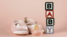 Pink soother falling in front of baby shoes and ba Footage