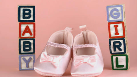 Baby shoes falling between baby blocks Stock Video Footage