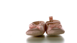 Baby shoes falling and bouncing on white surface Stock Video Footage