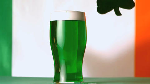 Large green shamrock falling beside pint of green Stock Video Footage