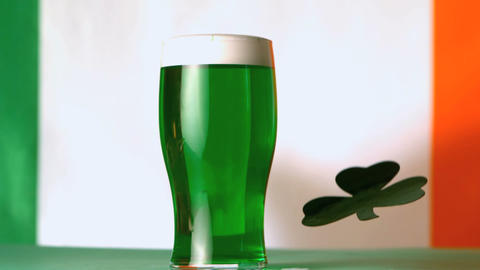 Large green shamrock falling beside pint of green  影片素材