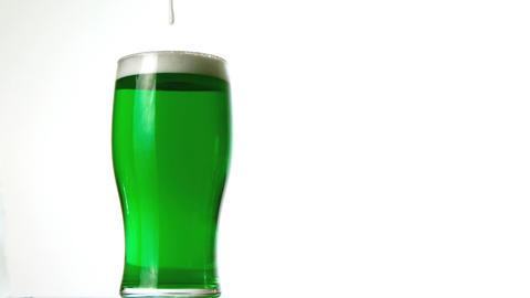 Foam pouring onto pint of green beer 影片素材