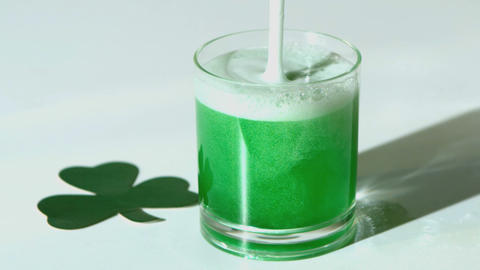Green beer pouring into tumbler beside paper shamr Footage