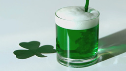 Green beer pouring into a tumbler beside paper sha 影片素材