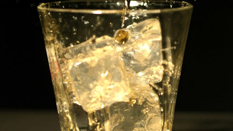 Whiskey pouring into tumbler with ice close up Footage