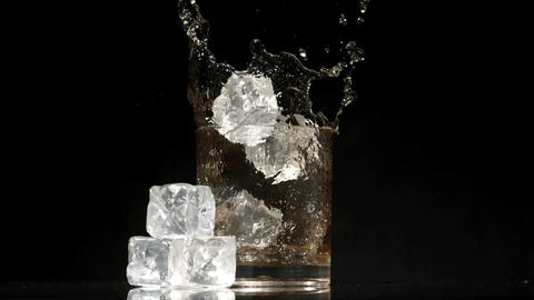 Ice cubes falling into glass of whiskey and ice on black background Footage
