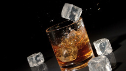 Three ice cubes falling into tumbler of whiskey and ice Live Action