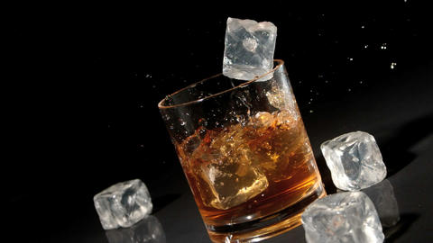 Three ice cubes falling into tumbler of whiskey an Stock Video Footage