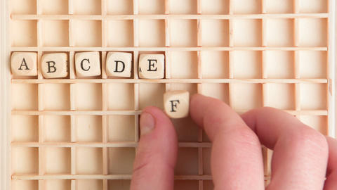 Hand spelling out the alphabet in wooden dice on a Stock Video Footage