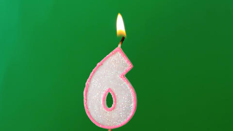 Six birthday candle flickering and extinguishing on green... Stock Video Footage