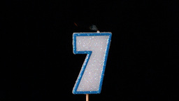 Seven birthday candle flickering and extinguishing on black background Footage