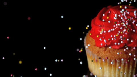 Colourful sprinkles pouring onto cupcake on black Stock Video Footage