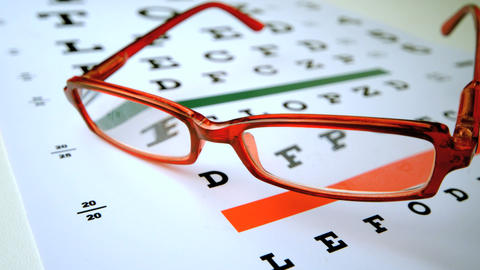 Red reading glasses falling onto eye test Footage