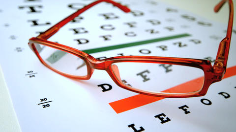 Red reading glasses falling onto eye test Stock Video Footage