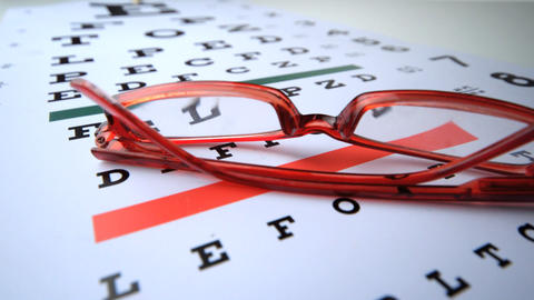 Red reading glasses falling onto eye test close up Stock Video Footage