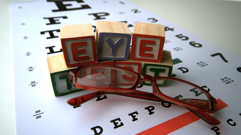 Glasses falling onto eye test with blocks spelling Footage
