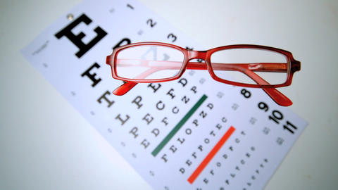 Red reading glasses falling onto an eye test overh Footage