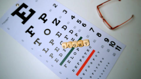 Dice spelling out sight falling onto eye test beside glasses Footage