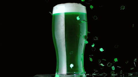 Shamrock confetti falling in front of pint of gree 影片素材