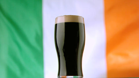 Pint of Irish stout on background of irish flag wa 影片素材