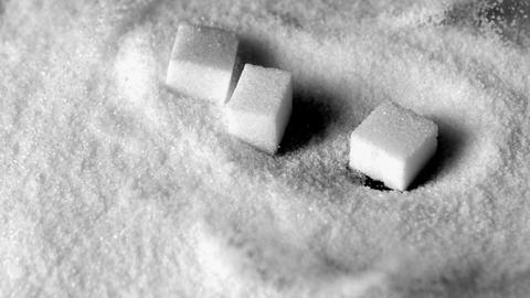 Sugar cubes falling in pile of sugar Live Action