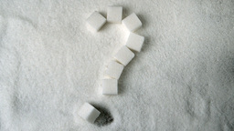 Question mark spelled in sugar cubes forming on pile of sugar Live Action