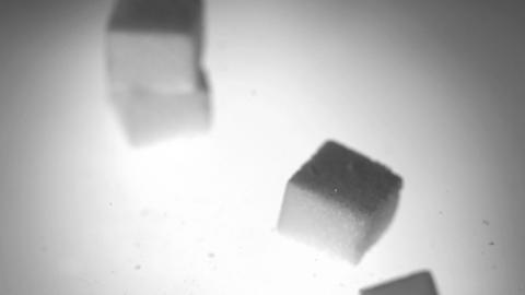 Four sugar cubes falling on white surface Footage