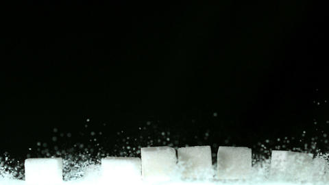 Sugar cubes falling onto pile of sugar Live Action