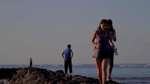 2 women walk along the rocks at waikiki beach Footage