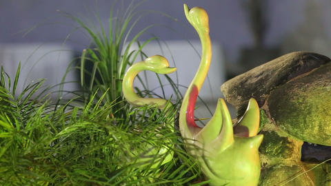 decorative green swans are near the rocks Stock Video Footage