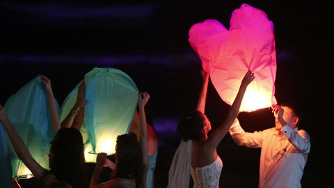 bride and groom lit a Chinese lantern on the beach Footage