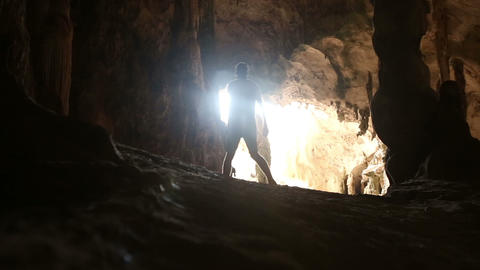 a man walked into the cave and looking Footage