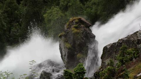 Water in waterfalls hitting a big rock Stock Video Footage