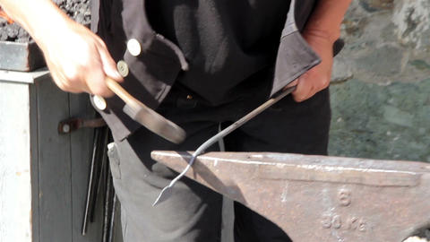 A blacksmith bending hammering of a metal or steel Footage